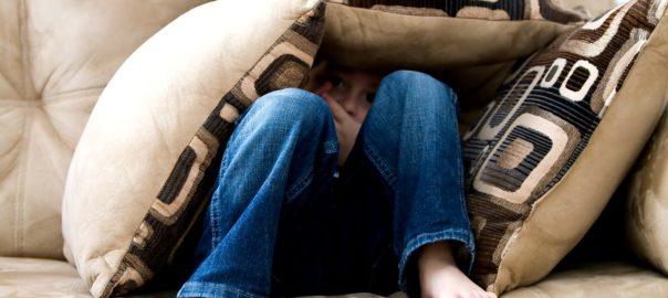 Feiger Junge unter Kissen