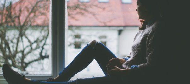 Frau in einer Fernbeziehung am Fenster