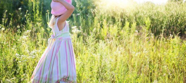 kleine Frau mit Hut auf Wiese