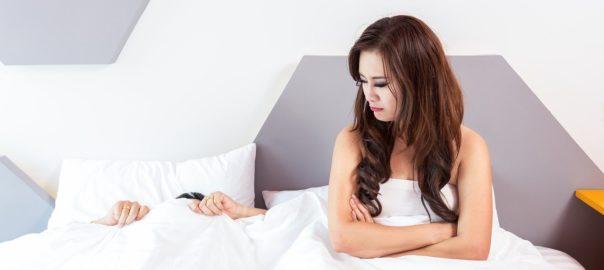 Frau im Bett zickt mit ihrem Freund